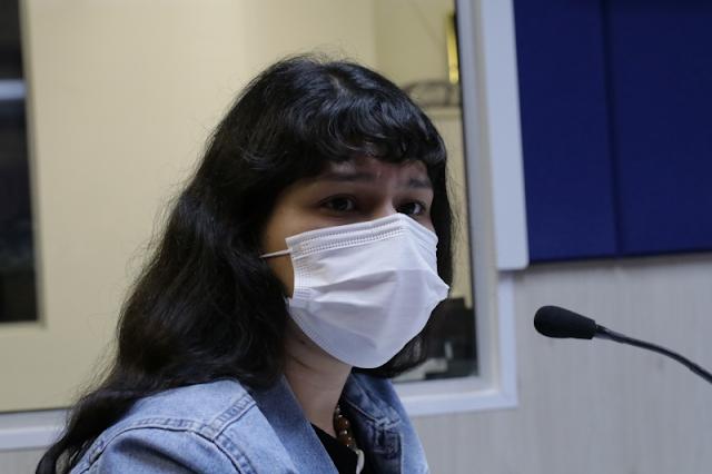 A imagem mostra Renata usando máscara e uma jaqueta jeans. Ela está de lado em frente a um microfone.