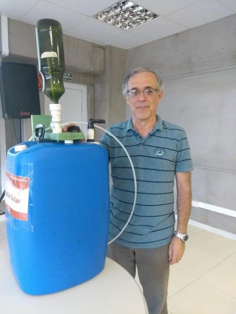 A foto mostra o irrigador com o seu inventor: um homem, branco, cabelos grisalhos, usa óculos quadrados, veste camiseta polo azul com listras pretas e calça jeans.