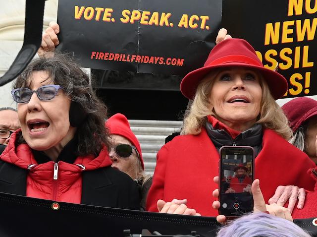 A imagem mostra as atrizes Lily Tomlin e Jane Fonda gritando em um protesto. Elas são brancas e usam casacos de frio.