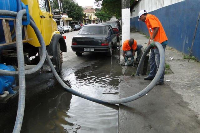 Trabalhadores fazem a limpeza dos bueiros