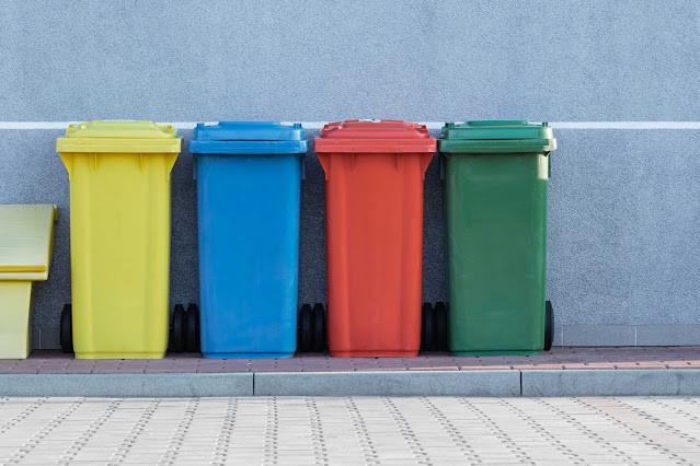 A foto mostra latas de lixos para pôr lixos recicláveis. Amarela, azul, vermelho e verde.