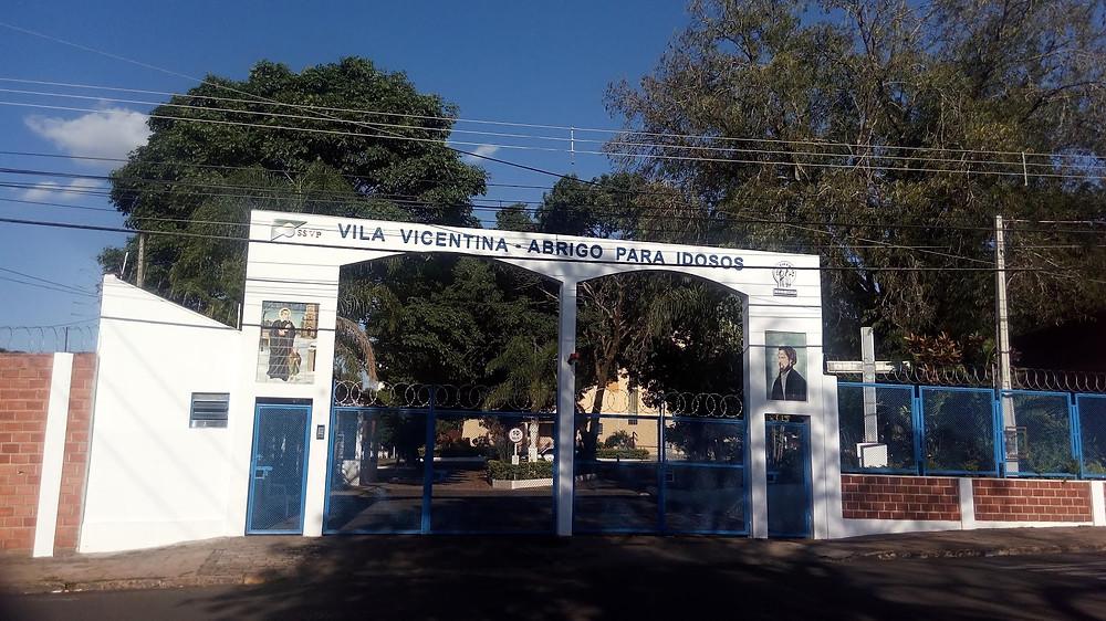 A foto mostra a entrada da Vila Vicentina, que é um abrigo para idosos e promove a venda de produtos usados em bazar.