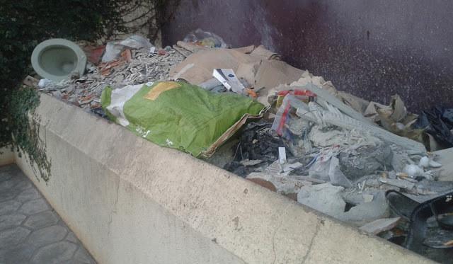 A foto mostra uma bancada na rua cheia de lixo e bagunça. Tem restos de construção e plásticos.
