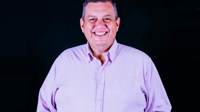 A imagem mostra Sérgio Alba sorrindo, ele veste uma camisa lisa lilás. Ele está em um fundo preto. As mãos estão no bolso.