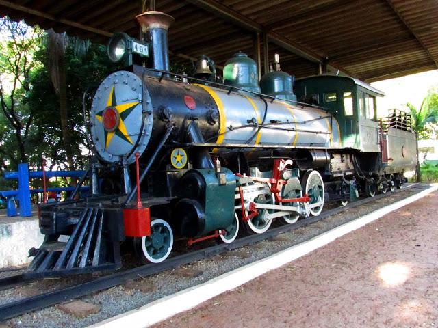 A foto mostra uma Maria Fumaça. O trem é azul, preto e tem listras amarelas. Na sua frente tem uma estrela de cinco pontas pintadas de amarelo e verde. As rodas tem detalhes branco e vermelho.