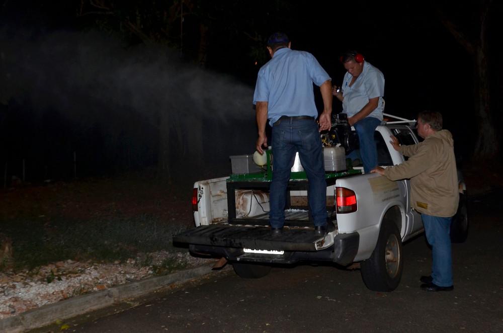 Homens em um carro fazem a nebulização contra mosquitos da dengue.