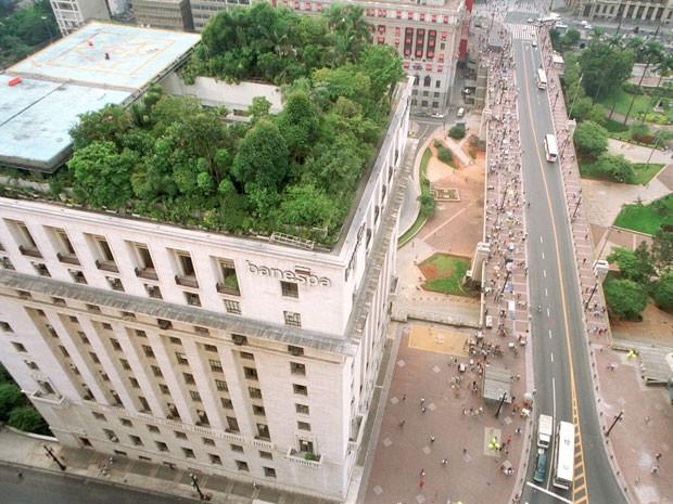 A foto foi tirada do alto. A foto mostra um prédio e no seu telhado tem plantas verdes. Lá embaixo se vê a rua e várias pessoas se movimentando.