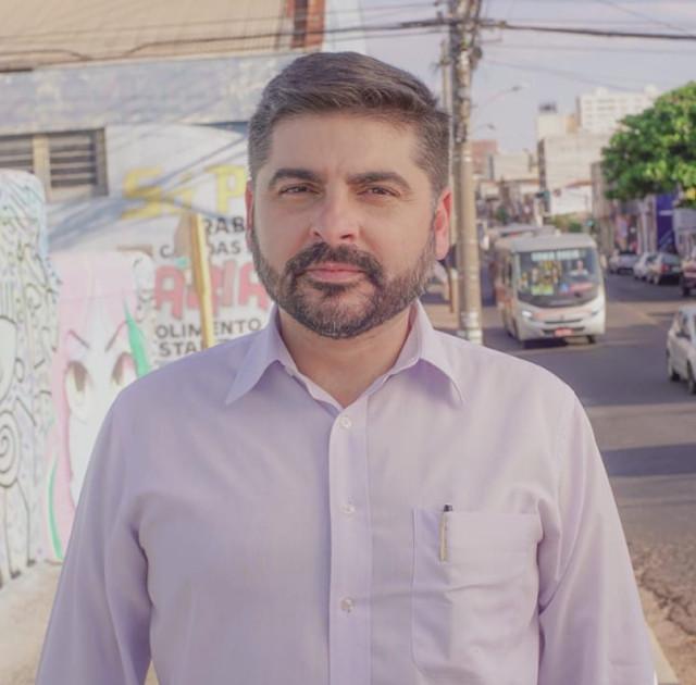 A imagem mostra Jorge olhando para a câmera sério. Ele veste uma camisa azul claro lisa. Ao fundo se vê o trânsito com o ônibus circular parado. E uma parede pichada.