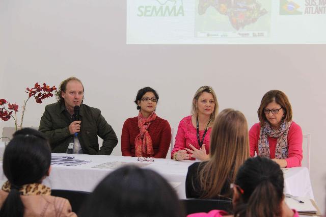 A foto mostra quatro pessoas sentadas de frente para uma mesa com toalha branca. Da esquerda para a direita: Pessoa 1: homem branco, ruivo, calvo, usa uma casaco preto. Pessoa 2: mulher branca, cabelo curto acima dos ombros castanhos, usa óculos retangulares, veste uma blusa comprida vermelha e está com um cachecol rosa avermelhado. Pessoa 3: mulher branca, loira, cabelo curto, usa uma blusa meia manga rosa salmão e um crachá. Pessoa 4: Mulher branca, cabelo castanho curto, veste blusa de frio rosa e usa um cachecol estampado de pequenas flores, ela também usa óculos.