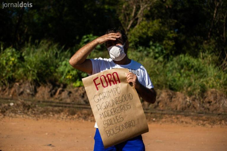 "Protestante contra a vinda do ministro Ricardo Salles segura cartaz com os direzes ""fora garimpo, agronegócio, madereiros, Salles e Bolsonaro""."