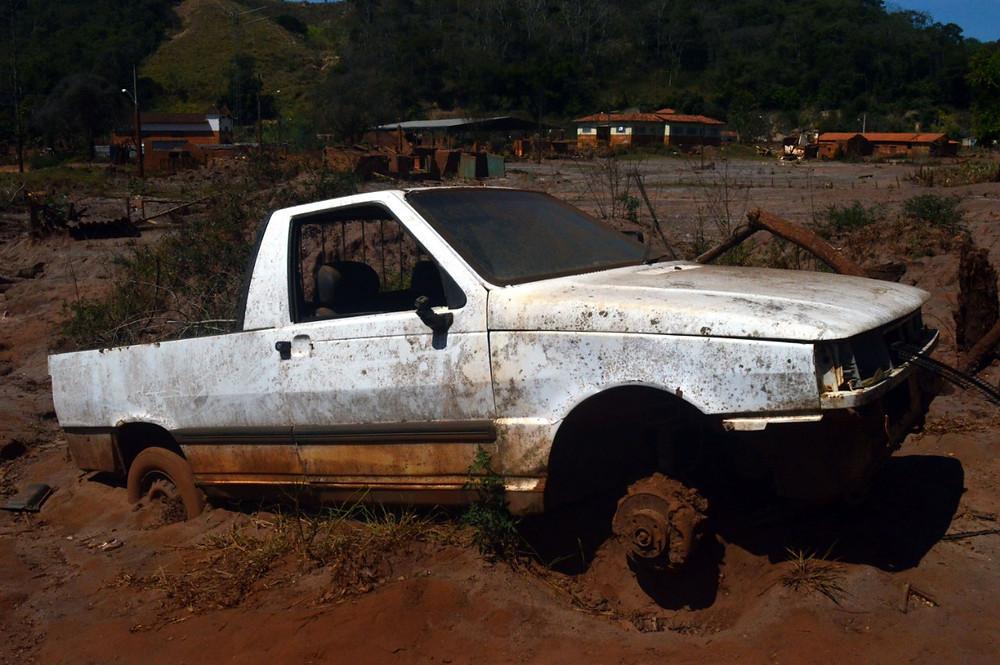 A foto mostra um carro que era branco abandonado e preso na lama.