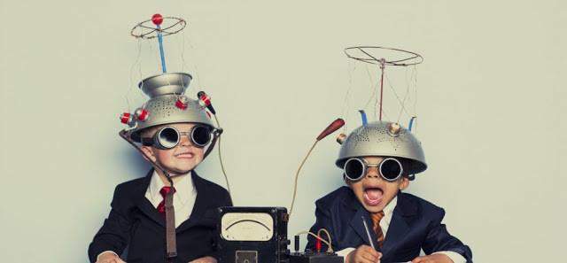 Duas crianças usam capacetes com fios conectados. Elas estão brincando.