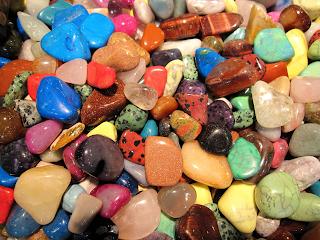 A imagem mostra muitas pedras pequenas coloridas. Elas estão todas juntas. As cores são azul claro brilhante, verde água, verde folha, vermelho, rosa, preto, branco translúcido, marrom, amarelo, roxo, cinza. Todas as pedras brilham indicando que há uma luz refletindo diretamente nelas.