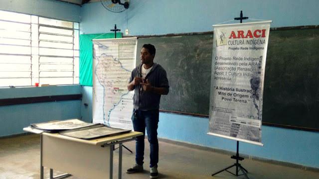 A foto mostra um homem indígena dando uma aula em uma sala. Ele veste calça jeans, camiseta e moletom. Na sala tem dois pôsteres, uma lousa e uma mesa.