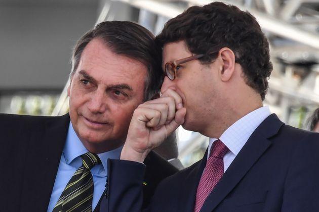 A imagem mostra o presidente Jair Bolsonaro e o Ministro do Meio Ambiente Ricardo Salles. Ricardo está falando alguma coisa no ouvido de Bolsonaro. O presidente está com um sorriso de canto. Os dois homens usam terno e gravata.