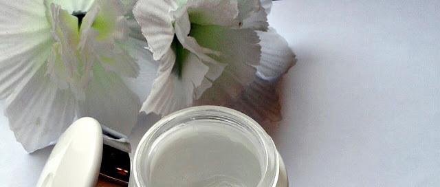 Canto esquerdo à cima uma flor falsa e abaixo no centro a metade de um pote redondo de algum cosmético.