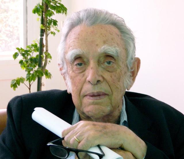A foto mostra um homem branco, idoso, cabelos brancos, usa terno, ele segura um papel enrolado e seus óculos.
