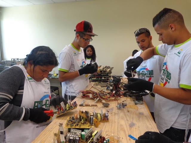 Jovens manipulando eletrônicos, eles fazem parte do projeto Eco-eletro