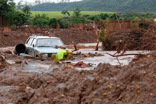 A foto mostra um carro, madeira e outros materiais encalhados na lama tóxica.