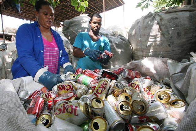 A foto mostra dois trabalhadores da coleta seletiva manuseando um grande saco de latinhas de cerveja e refrigerante.