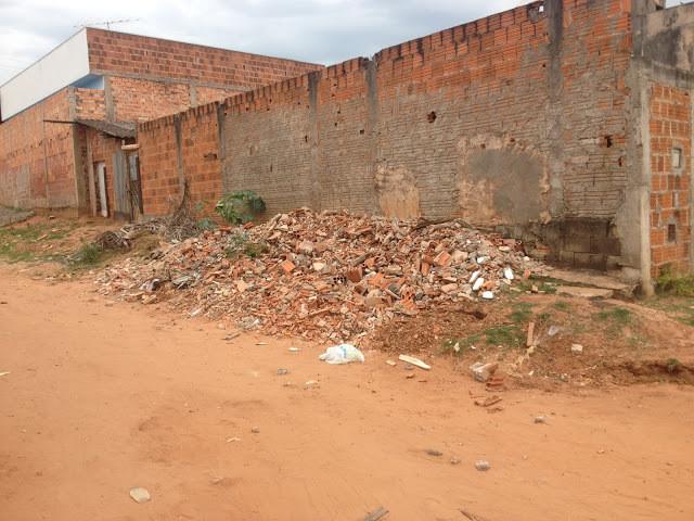 A foto mostra acúmulo de entulho - maioria de restos de construção jogados em um lugar inapropriado. Estão jogados ao lado de um muro, a rua é de terra.