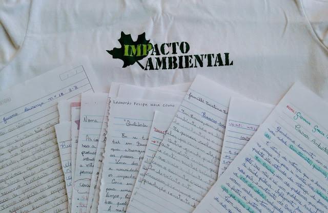 A foto mostra a camiseta escrito Impacto Ambiental. E embaixo vários papéis de redação dos alunos.