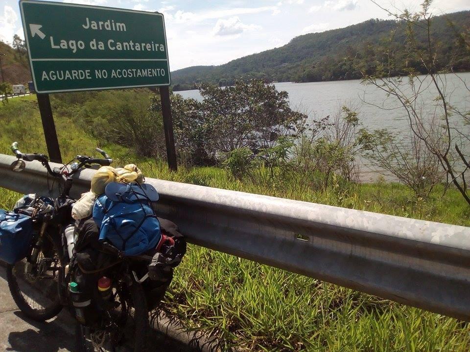 A foto mostra o lado de uma rodovia. Ao lado tem a reserva de água Cantareira. Uma placa indicando: Jardim Lago da Cantareira Aguarde no acostamento