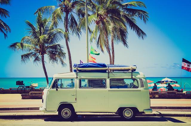 A foto mostra uma perua kombi estacionada em frente ao mar e palmeiras.