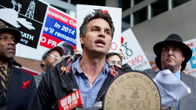 A imagem mostra o ator Mark Ruffalo em um protesto ambiental. Ele é caucasiano e veste uma jaqueta marrom, ele segura cartazes contra o fraturamento hidraúlico.