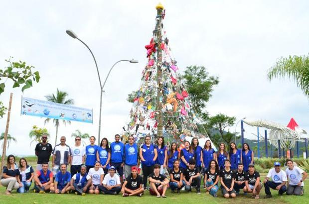 A foto mostra uma árvore alta feita de lixo retirado da praia. Pessoas posam na frente dela pois foram elas que coletaram o lixo.