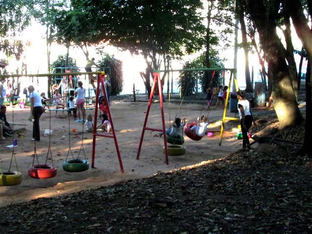A foto mostra crianças brincando no parquinho. A cena mostra dois balanços coloridos feitos de pneus, crianças estão no balanço do lado esquerdo. Ao fundo se vê arbustos e uma roda, onde as crianças brincam de girar. O dia está ensolarado.