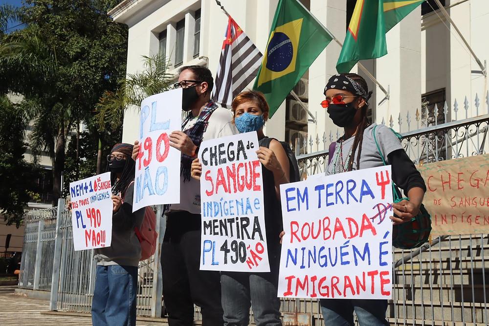 Manifestantes seguram cartazes contra o PL 490 em frente à Câmara Municipal de Bauru.