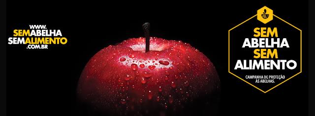 A foto mostra um fundo preto, no centro uma maça vermelha e molhada. No lado esquerdo, se lê www.semabelhasemalimento.com.br. E no lado direito se lê: Sem abelha, sem alimento. Campanha de proteção ao animal.