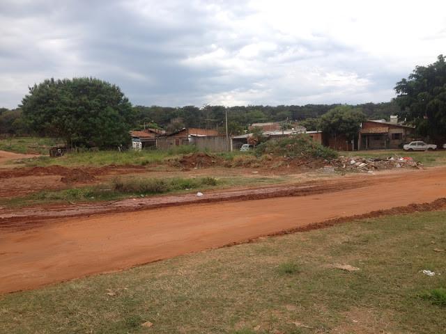 A foto mostra uma estrada de terra e um terreno vazio. Ao fundo se vê algumas casas.