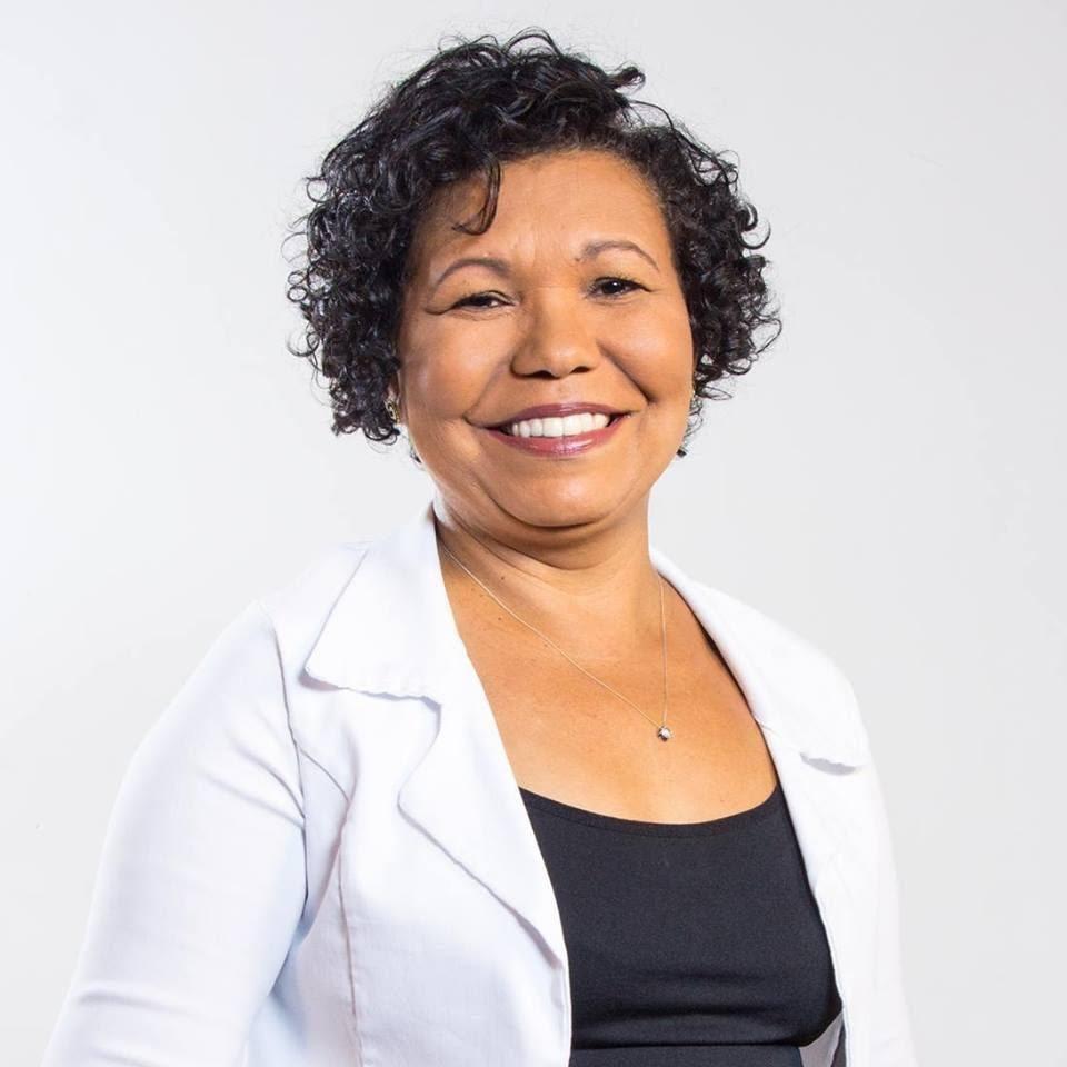 A foto mostra uma mulher negra, cabelo cacheado curto - na altura das orelhas. Ela sorri e tem olhos castanhos. Ela veste uma blusa preta e um blaser branco.