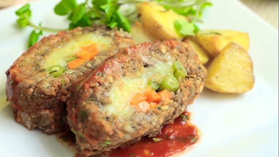 A imagem mostra dois rocamboles de lentilha e quinoa. Eles são recheados com vagem e estão em cima de um prato. Ao lado tem raminhos de cebolinha e batata assada cortada.