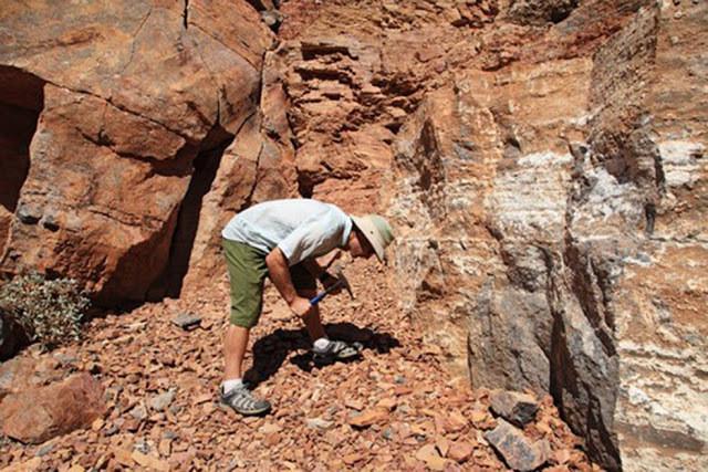A imagem mostra um canyon de pedra marrom. No meio vemos um homem branco, vestindo um chapéu branco, camiseta listrada azul, um short verde  e tênis. Ele segura uma picareta que está trabalhando em uma rocha ao lado do canyon. O sol está bem forte, fazendo sombras no lugar.