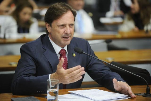 A foto mostra um homem branco, de terno, cabelo castanho, sentado na frente do microfone gesticulando.
