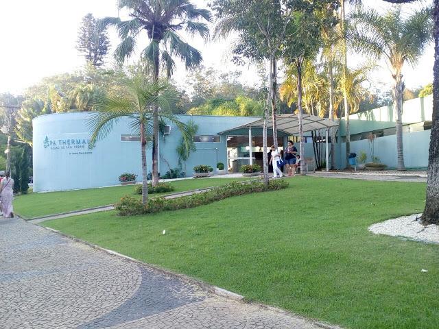 A foto mostra a frente do Thermas Spa, tem uma grama verde em frente. Há palmeiras no fundo e a construção tem paredes azuis.