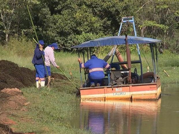 A foto mostra um homem dentro do barco e outras duas pessoas em terra medindo a altura do rio.