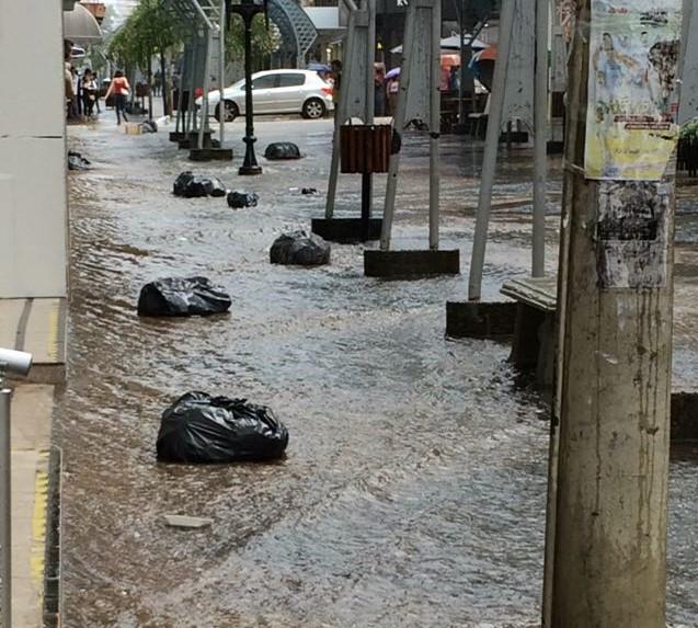 Calçadão da Batista (centro - comércio) alagado, com lixo escorrendo junto com a água.