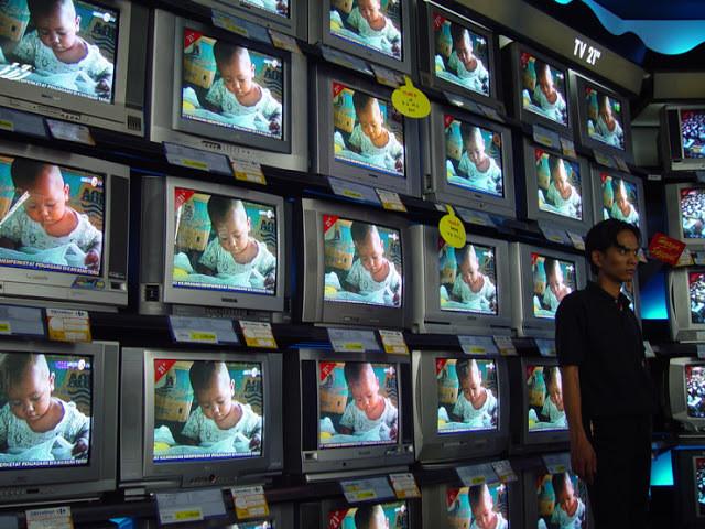 A foto mostra várias televisões uma do lado da outra, na tela mostra uma criança negra lendo. No canto, um homem branco está ao lado das televisões.