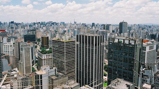 A foto mostra o grande número de prédios na cidade de São Paulo. Feitos de concreto e alguns espelhados.