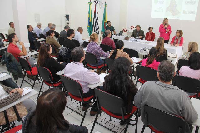 A foto mostra uma reunião em uma sala fechada. As pessoas estão sentadas em fileiras horizontais, assistindo quatro pessoas sentadas em uma mesa uma do lado da outra. Uma mulher segura o microfone e está em pé. A parede da sala é branca.