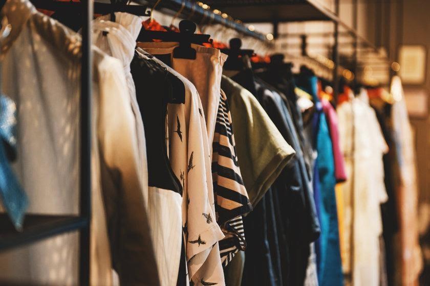 A foto mostra roupas penduradas em araras de loja.