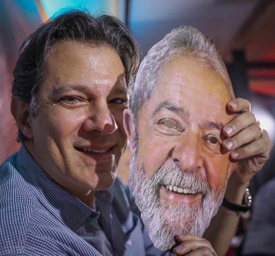 Fernando Haddad sorri e segura uma máscara do rosto do Lula. Haddad é um homem branco, cabelos castanhos e têm covinhas, ele veste uma camisa azul com listras brancas. Lula é homem, branco, idoso, e com cabelos brancos e barba branca.