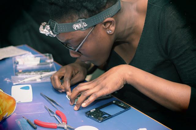 Uma mulher seleciona peças de um celular.