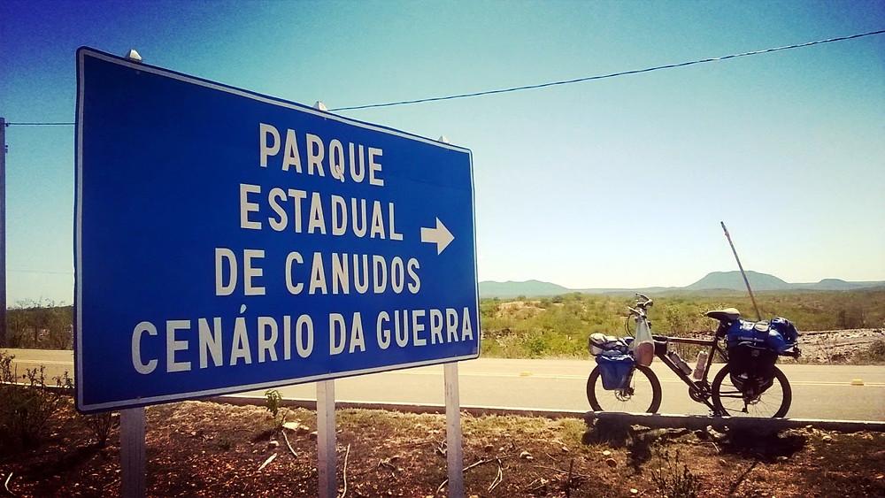 A foto mostra uma placa escrito: Parque Estadual de Canudos Cenário de Guerra. Ao lado uma bicicleta com mantimentos de viagem.