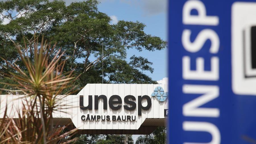 A imagem mostra a fachada do câmpus da Unesp de Bauru com o letreiro da universidade.
