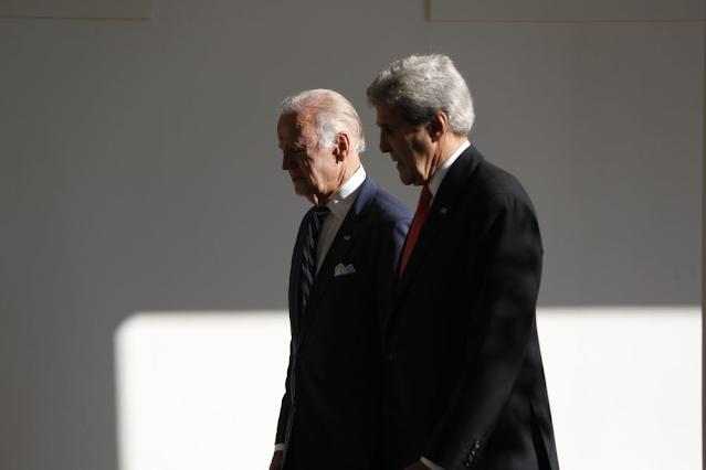 A imagem mostra Joe Biden e John Kerry andando lado a lado. A foto foi tirada da lateral dos homens. Eles são caucasianos. Joe usa um terno azul e gravata listrada com azul e branco. E John usa um terno preto com gravata vermelha. Ambos tem cabelos brancos.